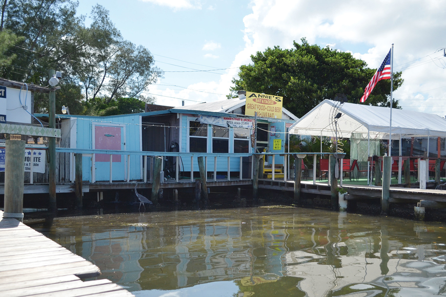 Photo of Annie's Bait and Tackle with water showing below the docks the shop sits on.