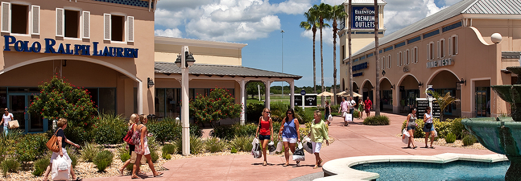 Photo of 3 women walking and shopping at Ellenton Premium Outlets while holding multiple pastic bags full of purchases.