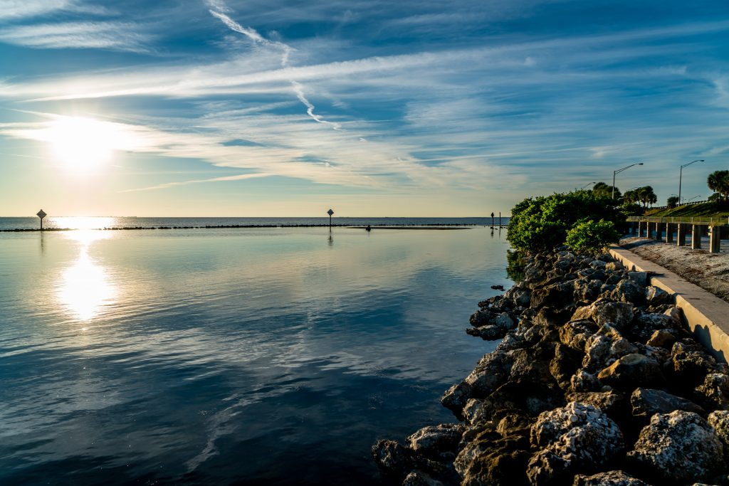 The magnificent beauty of Terra Ceia Aquatic Preserve in west central Florida. The sun can be seen reflecting off og the water. There is a seawall made of rocks on the right-hand side of the frame.