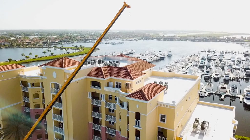 Photo of a construction crane lifting up an air conditioning unit to the roof of Riviera Dunes condominiums as an Air & Energy technician guides it to place.